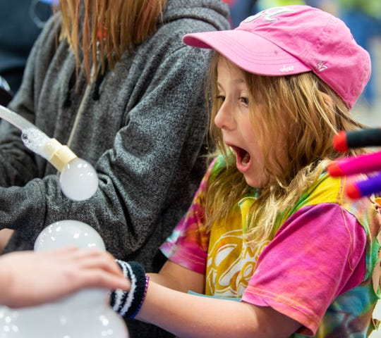Allison Noury, 8, from Cottonwood Elementary, reacts to holding a sublimated CO2 bubble at Fernley High School's STEM Festival.