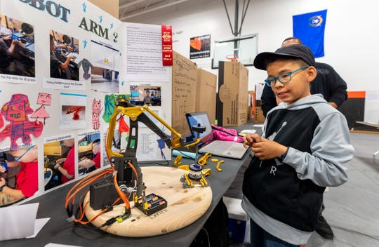 Derrell Dunbar, 8, from Cottonwood Elementary, demonstrates a robotic arm which he built from 3D parts he printed at home, and entered in the science fair at Fernley High School's STEM Festival.