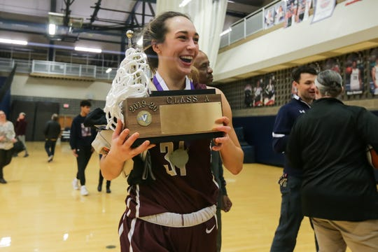 Katie Bischoping (31) of Pittsford Mendon carries the trophy to get a team photo after beating Irondequoit in the Section V Class A championship game at Gates Chili on March 6, 2020.