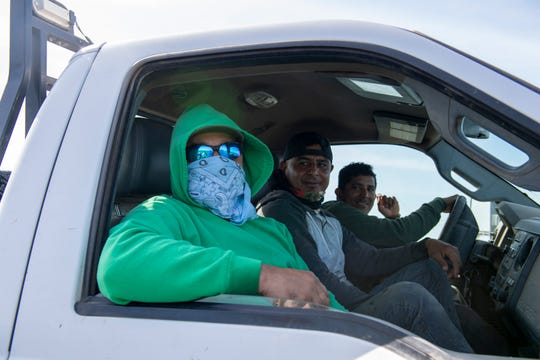 Juan Manuel Virgin, left, and Daniel Lopez Avilez, middle, sit inside a pickup truck as they talk about the difficulties they face when trying to find respiratory protection. March 04, 2020.