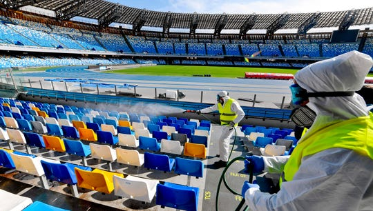 Workers with protective suits sanitize the seats of the San Paolo stadium in Naples, Italy, on March 4.