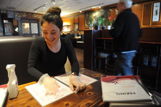 "Dayana Salguero, hostess at Peking Restaurant in Ventura, wipes down menus with 70% isopropyl alcohol. It's one of several measures put in place by owner Yunping ""Margaret"" Qiu to help maintain the health of the restaurant's workers and patrons amid fears about the flu and coronavirus."