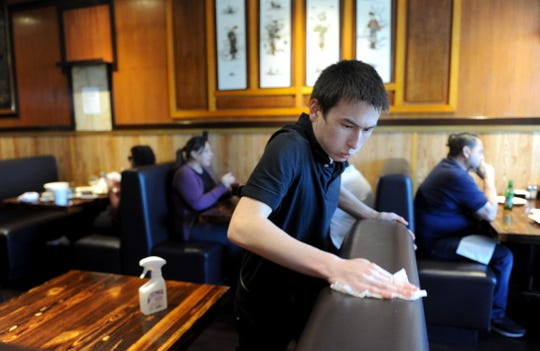 "Benjamin Lilienfeld, a waiter at Peking Restaurant in Ventura, helps with a restaurant-wide wipe down using 70% isopropyl alcohol. The restaurant's owner, Yunping ""Margaret"" Qiu, instituted the procedure in late January to help maintain the health of workers and patrons alike amid concerns about the flu and coronavirus."