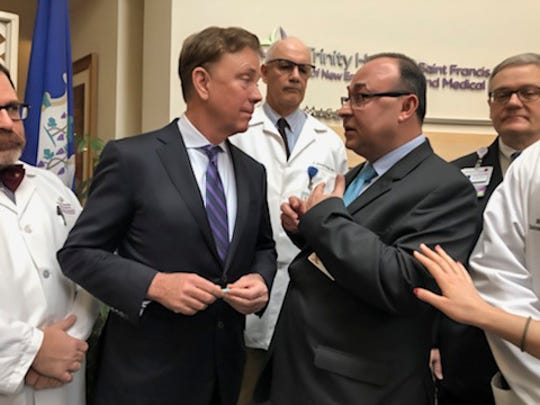 Connecticut Gov. Ned Lamont, second from left, listens to Dr. Danyal Ibrahim, second from right, regional chief quality officer for Trinity Health Of New England, following a news conference about the state's response to the new coronavirus at St. Francis Hospital and Medical Center in Hartford, Conn., Friday, March 6, 2020. (AP Photo/Susan Haigh)