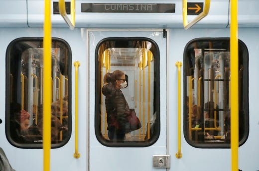 A woman wearing a face mask stands in a subway train in Milan, Italy on March 5, 2020. The focal point of the coronavirus emergency in Europe, Italy, is also the region's weakest economy and is taking an almighty hit as foreigners stop visiting its cultural treasures or buying its prized artisanal products, from fashion to food to design. EuropeÕs third-largest economy has long been among the slowest growing in the region and is the one that is tallying the largest number of virus infections outside Asia.