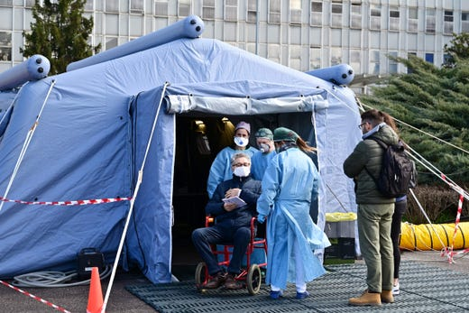 A man receives assistance in a pre-triage medical tent in front of the Cremona hospital, in Cremona, Italy, on March 4, 2020.