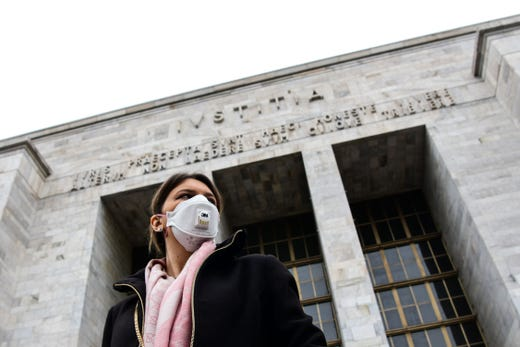 A woman wearing a respiratory mask exits from the Palace of Justice in Milan, on March 5, 2020.  Italy closed all schools and universities until March 15 to help combat the spread of the novel coronavirus crisis. The government decision was announced moments after health officials said the death toll from COVID-19 had jumped to 107 and the number of cases had passed 3,000.