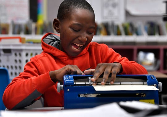 Audace Museveni a second grade student at Thomas Elementary, laughs as he writes on his Brailler Feb. 28. The typewriter-like machine writes in Braille, which Audace proofreads with his fingers as he goes along.