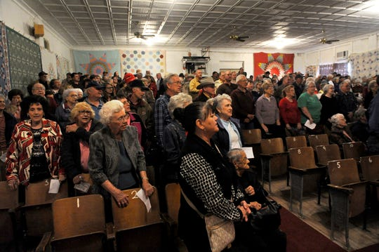 Audience members stand and sing along with a hymn prior to the start of the 2014 Hee Haw inside the Sagerton Community Center.