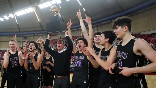 North Kitsap boys basketball coach Scott Orness lifts the Class 2A state championship trophy with his team at the Yakima Valley SunDome.