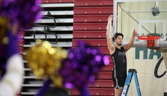 North KItsap's Shaa Humphrey cuts down one of the nets after their 56-53 win over Clarkston at the Yakima Sun Dome on Saturday, March 7, 2020.
