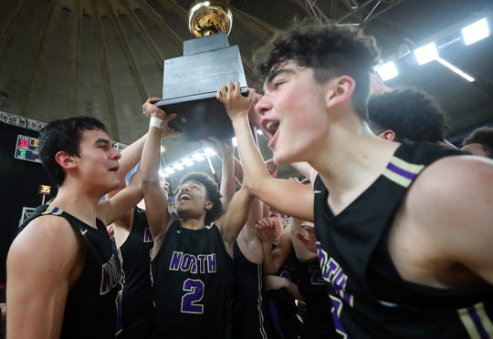 North Kitsap celebrates winning the Class 2A state championship trophy after Saturday's 56-53 victory over Clarkston at the Yakima Valley SunDome.