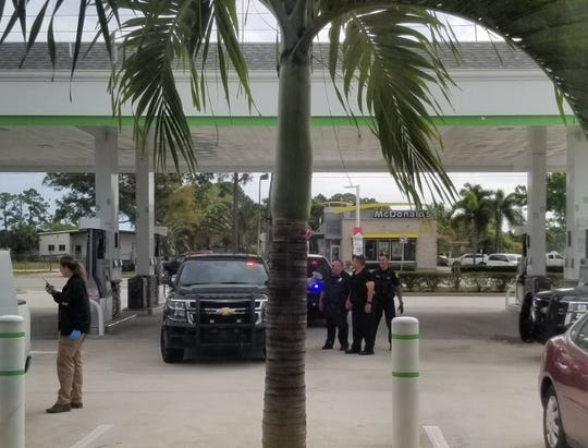 """Law enforcement officers stand in the Cumberland Farms parking lot Sunday morning after the """"person of interest"""" was arrested."""