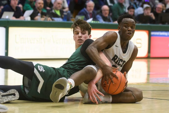 St. Johnsbury's Andrew Cowan (24) battles for the loose ball with Rice's Michel Ndayisahimiye (2) during the boys high school DI basketball championship game between the St. Johnsbury Hilltoppers and the Rice Green Knights at Patrick Gym on Sunday afternoon March 8, 2020 in Burlington, Vermont.