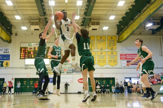 Rice's Michel Ndayishimiye (2) leaps for a layup during the boys high school DI basketball championship game between the St. Johnsbury Hilltoppers and the Rice Green Knights at Patrick Gym on Sunday afternoon March 8, 2020 in Burlington, Vermont.