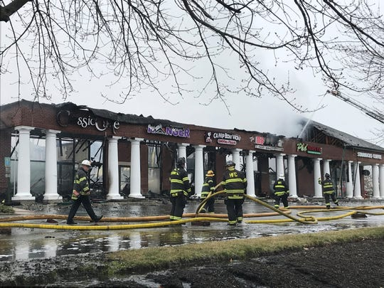 Firefighter walk past burned-out shops at the Short Hills Town Center on Friday morning