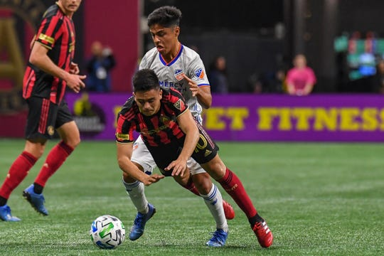 Mar 7, 2020; Atlanta, Georgia, USA; Atlanta United midfielder Gonzalo Martinez (front) is knocked over from behind by FC Cincinnati midfielder Frankie Amaya (behind) while playing the ball during the first half at Mercedes-Benz Stadium. Mandatory Credit: Dale Zanine-USA TODAY Sports