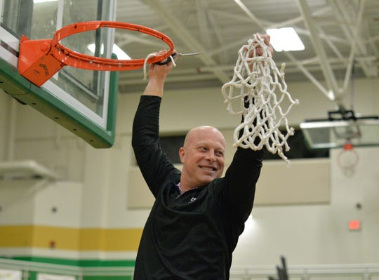 CHCA head coach Brian Lawhon holds up the net after beating Stivers in the OHSAA Division III playoffs at Northmont High School, Saturday, March 7, 2020
