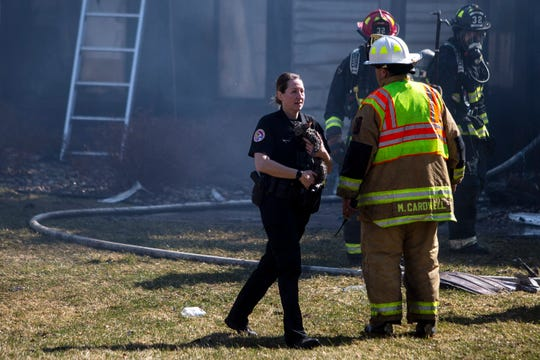 A police officer carries a cat rescued from the fire damaged building in the Ashford Ridge apartment complex on Sunday, March 8, 2020, in Urbandale.