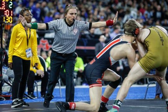 Cassandra Baranoski of Grand Rapids, referees the match between Brighton's Sam Freeman and Holt's Dylan Phelps during MHSAA Division 1 130 pounds wrestling individual finals at Ford Field in Detroit, Saturday, March 7, 2020.