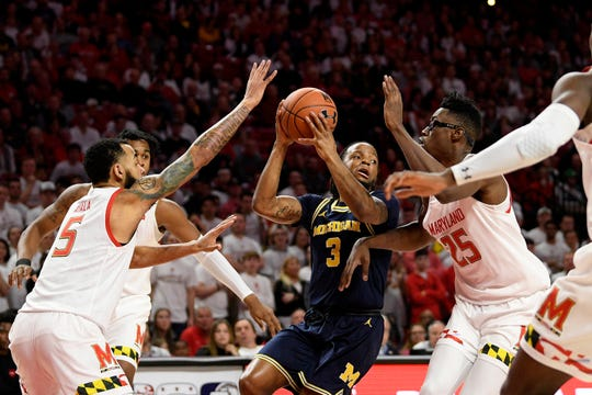 Michigan guard Zavier Simpson looks to pass against Maryland forward Jalen Smith (25) and guard Eric Ayala (5) during the first half Sunday, March 8, 2020, in College Park, Md.