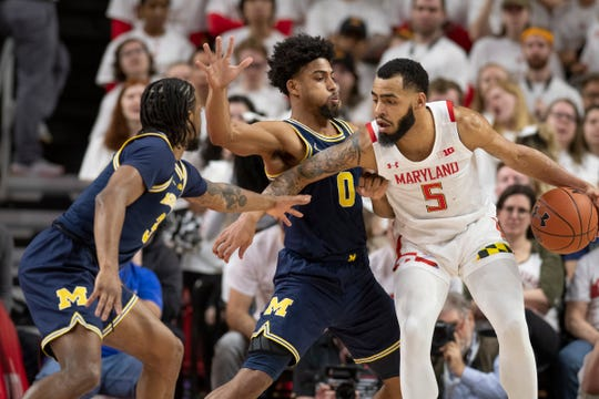 Maryland guard Eric Ayala dribbles as Michigan guards David DeJulius (0) and Zavier Simpson defend during the first half Sunday, March 8, 2020, in College Park, Md.