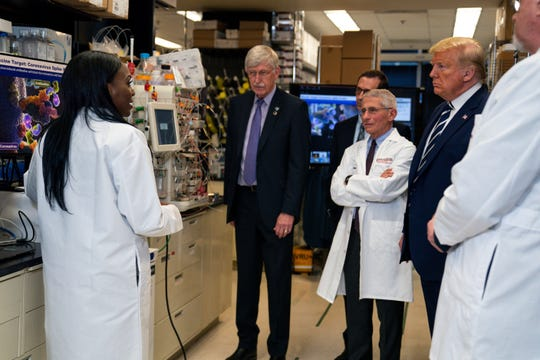 Dr. Kizzmekia Corbett, left, senior research fellow and scientific lead for coronavirus vaccines and immunopathogenesis team in the Viral Pathogenesis Laboratory, talks with President Donald Trump as he tours the Viral Pathogenesis Laboratory at the National Institutes of Health in Bethesda, Md.