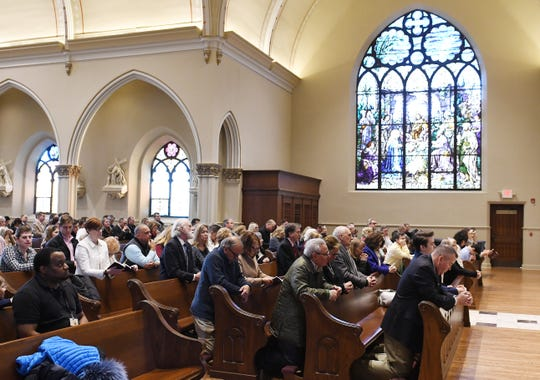 Parishioners pray during morning services at St. Paul on the Lake Catholic Church.
