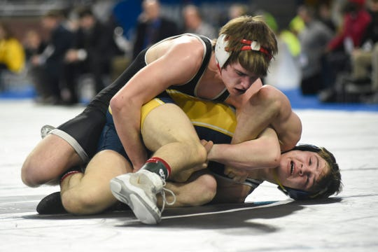 Austin Boone of Lowell, top, wrestles with Chayse LaJoie of Gaylord in the 145-pound title match.