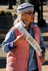 Susan Fowler of Evansville adjusts her sash before the commemorative Women's Suffrage March at the Civic Center Sunday afternoon.
