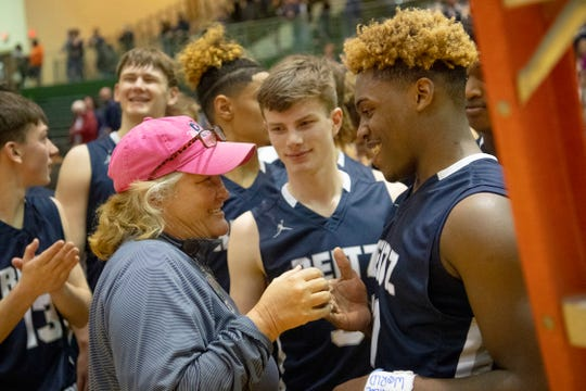 Reitz Athletic Director Beth Hagan congratulates Reitz's Mar'Quon Givens (11) and Reitz's Logan Martin (3) before handing them the scissors to cut down the net after beating Castle in the championship game of the IHSAA 4A Boys basketball sectional at North High School Saturday night, March 7, 2020.