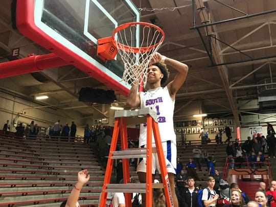 South Spencer junior Jace Kelly, who was named the sectional MVP, cuts down a piece of the net following the Rebels sectional championship victory.