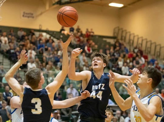 Reitz's Gavin Schippert (44), Reitz's Logan Martin (3) and Castle's Bob Nunge (30) go for a rebound during the championship game of the IHSAA 4A Boys basketball sectional at North High School Saturday night, March 7, 2020.