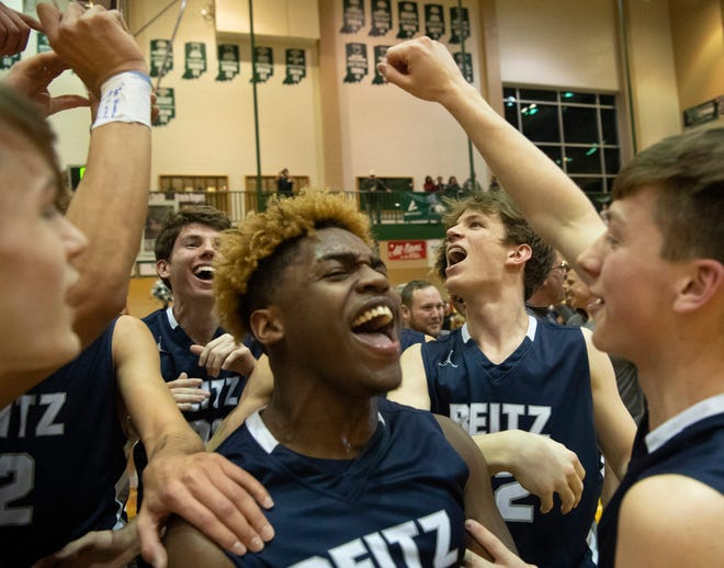 The Reitz Panthers celebrate their win over Castle in the championship game of the IHSAA 4A Boys basketball sectional at North High School Saturday night, March 7, 2020.