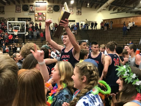 Blake Sisley holds the Class 3A Boonville Sectional championship trophy aloft after Heritage Hills ousted Memorial 79-53 on Saturday night. He scored 20 points.