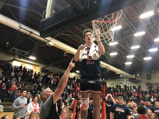 Simon Scherry, who scored a game-high 23 points, cuts down the nets after Heritage Hills won its first sectional title since 2003.