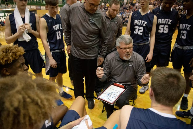 Reitz Head Coach Michael Adamsgoes over late-game plays against Castle during the championship game of the IHSAA 4A Boys basketball sectional at North High School Saturday night, March 7, 2020.