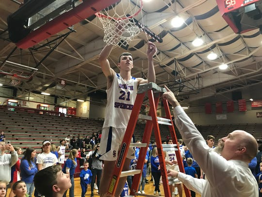 Matthew Smith, one of three seniors on South Spencer's roster, cuts piece of the net following the Rebels 56-55 sectional championship victory over North Posey.