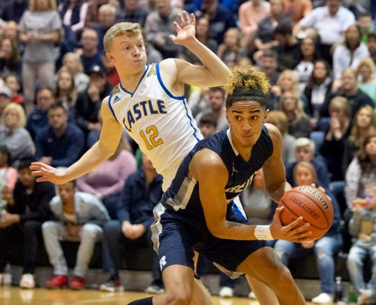 Reitz's Khristian Lander (4) is guarded by Castle's Jackson Mitchell (12) during the championship game of the IHSAA 4A Boys basketball sectional at North High School Saturday night, March 7, 2020.