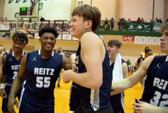 Reitz's Gavin Schippert (44) is congratulated by Reitz's Jason Cox after beating Castle in the championship game of the IHSAA 4A Boys basketball sectional at North High School Saturday night, March 7, 2020.