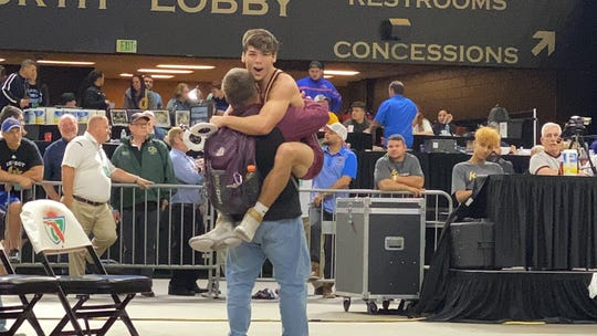 Riverdale wrestler Jared Dinh jumps into Raiders coach Keith Evans' arms after wining the Class 3A 138-pound state title March 7, 20202 at the FHSAA State Wrestling Championships in Kissimmee.