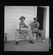 """The Library of Congress labels this image, """"Melrose, Natchitoches Parish, Louisiana. Mulattoes sitting on the porch of country store and barn near John Henry cotton plantation,"""" but to Jim Llorens,  it's his dad as a young man with a friend close to the Henry cotton plantation where he worked."""