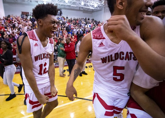 Lawrence North High School senior Tony Perkins (12), left, reacts as the team celebrates defeating Warren Central High School in an IHSAA boys' sectional championship basketball game, Saturday, March 7, 2020, at Lawrence Central High School. Lawrence North won 61-59.