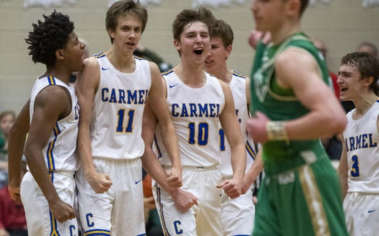 Carmel High School boys players celebrate their win over Westfield High School at Noblesville High School, Saturday, March 7, 2020. Carmel HS won the sectional title 54-41.