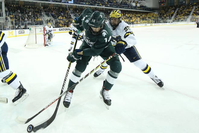Michigan State forward Adam Goodsir, left, battles for the puck in the corner with Michigan defenseman Keaton Pehrson, right, in the first quarter of the game between the Spartans and Wolverines at Yost Ice Arena on Saturday, March 7. Michigan defeated MSU 3-0 to advance to the Big Ten semifinals.