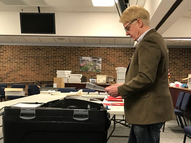 Meridian Township Treasurer Phil Deschaine tests a ballot tabulator March 8 during a public test of the township's voting equipment.