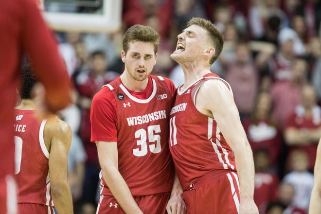 Wisconsin forwards Nate Reuvers (35) and Micah Potter celebrate during a timeout in a game in March.
