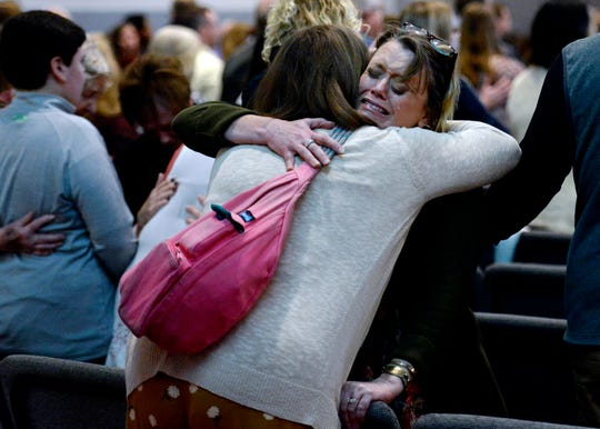 A parishioner cries as she is comforted during  a prayer for victims of the destructive tornados that ripped through Putnam County last Tuesday during a church service at Collegeside Church of Christ on Sunday, March 8, 2020, in Cookeville, Tenn.