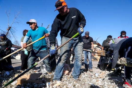Volunteers work into the day to shovel up debris from homes that were damaged heavily during the tornado on Albee Drive of the Hermitage neighborhood in Nashville, Tenn., on Saturday, March 7, 2020.