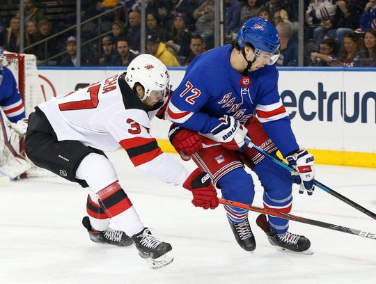 New York Rangers center Filip Chytil (72) and New Jersey Devils center Pavel Zacha (37) battle for position during the first period at Madison Square Garden.